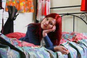 Scarlet haired schoolgirl Krystin stripping and smiling in her bedroom